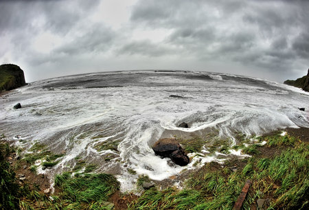 fisheye landscape of waves crushing at the sandy shore, storm at the beach,