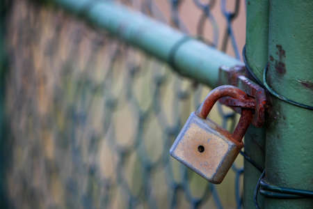 keep gate closed: Old padlock on green gate without key Stock Photo