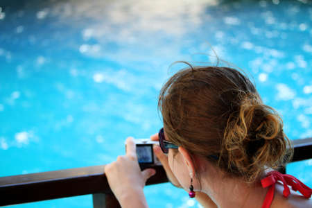 Young woman makes photo with camera on the holiday
