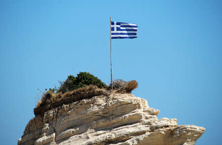 Greece flag on the cliff at the sea