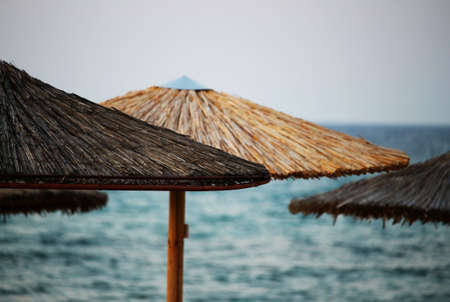 Wooden sun parasols at beach by the sea
