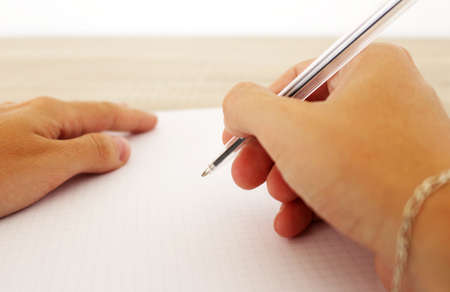 Man is writing on the paper with pen