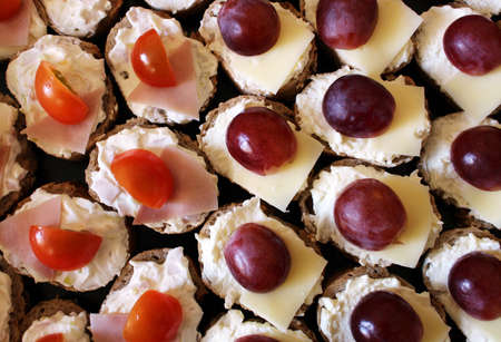 Detail of cheese savory with ham, tomato and grape