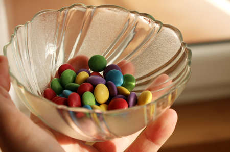 Man is holding bowl with chocolate candies