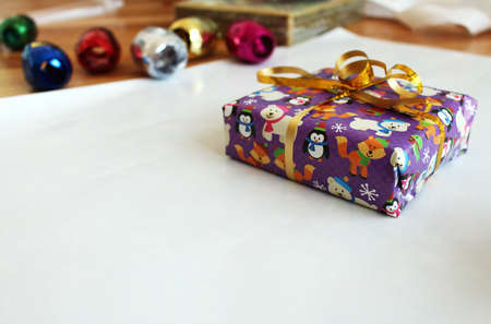 Packing purple christmas gift package with ribbon