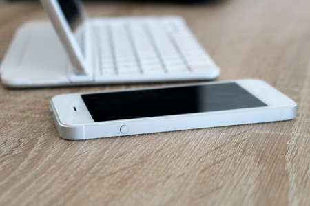 White cellphone and tablet with keyboard on table