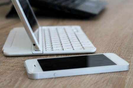 Office workspace with mobile phone and tablet