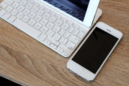 White smartphone and white tablet with keyboard