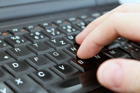 Man is writing with keyboard of laptop