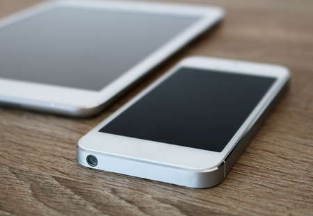 Detail of white mobile phone and white tablet