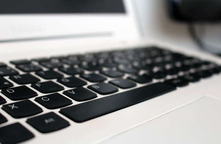 White laptop keyboard with black buttons in office