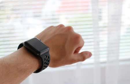Mans hand with black smart watch in office Reklamní fotografie
