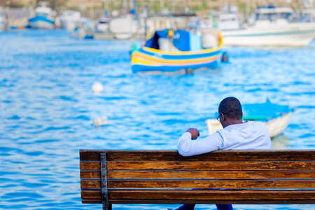 phoenicians: Tourist reading a book on the bench in the port of Malta Stock Photo