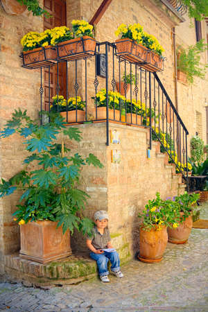 spello: Child sitting in an alley holding a map of the town of Spello (Umbria, Italy) Stock Photo