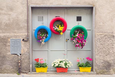 planters: Ingenious, original and environmentally friendly method of recycling of tires car as planters in a village in Tuscany Stock Photo