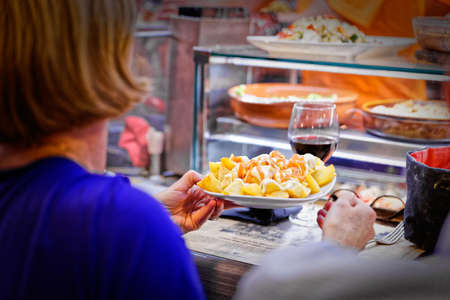 restaurateur: A woman picks up her first dish ready in a market stall at La Boqueria in Barcelona Stock Photo