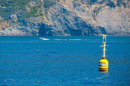 inshore: Inshore yellow buoy floating in the deep blue sea, warning concept, reporting