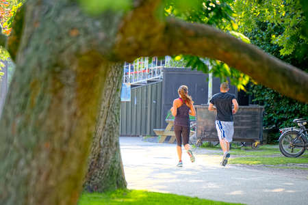 avenues: Couple jogging in the leafy avenues of Vondelpark Stock Photo