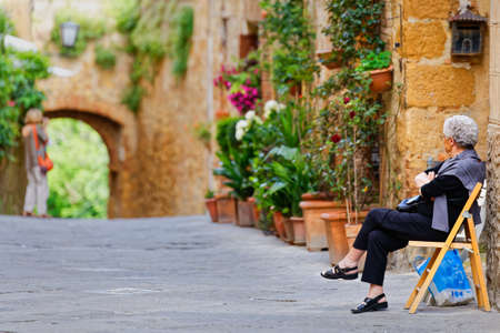valdorcia: Elderly woman rests on a chair in the street in Pienza Stock Photo