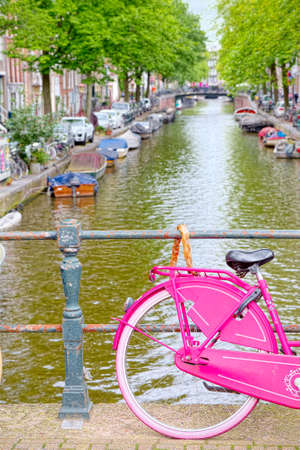 pink bike: Pink bike on a stopover in Amsterdam canal