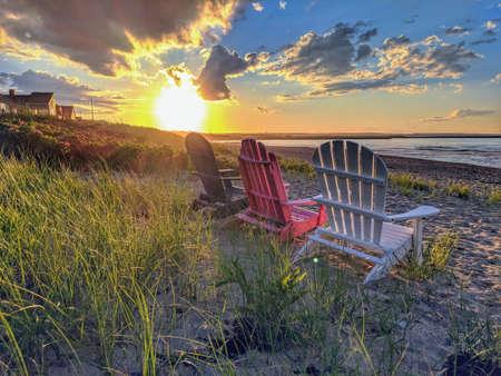 Rote weiße und blaue Stühle bei Sonnenuntergang