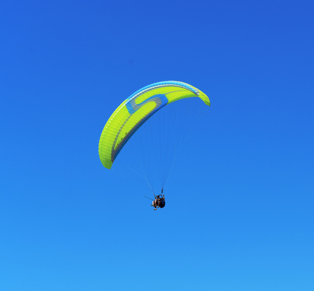 yellow blue paraglider on blue sky Imagens