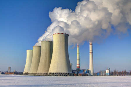 factory power generation: chimneys of coal-fired power plants in the winter snowy landscape Stock Photo