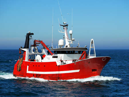 Red fishing boat underway at sea to fishing grounds.