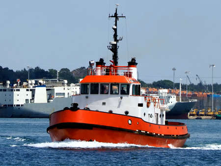 Red Tugboat underway in harbour boundries to towing assistance operation.