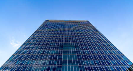 headquarter: Glass reflective office buildings against blue sky with clouds and sun light Stock Photo