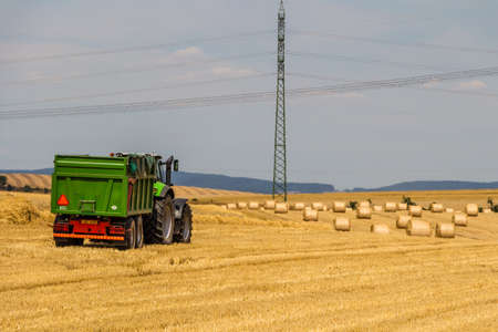 yielding: Tractor harvester working in wheat field in summer time