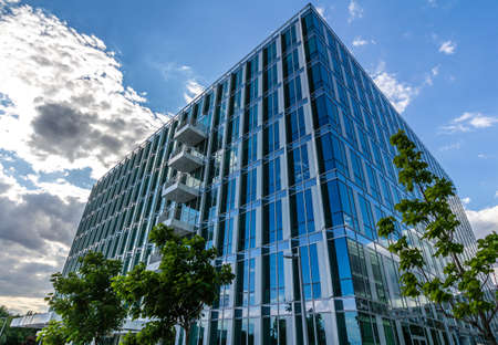 real estate industry: Glass reflective office buildings against blue sky with clouds and sun light Editorial