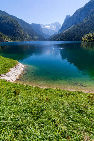 valley view: Beautiful landscape of alpine lake with crystal clear green water and mountains in background, Gosausee, Austria Stock Photo