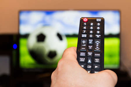 Watching soccer  football game on modern tv, with a close-up of the remote control
