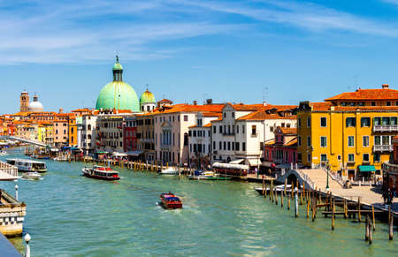 View of the canal with boats and gondolas in Venice, Italy. Venice is a popular tourist destination of Europe