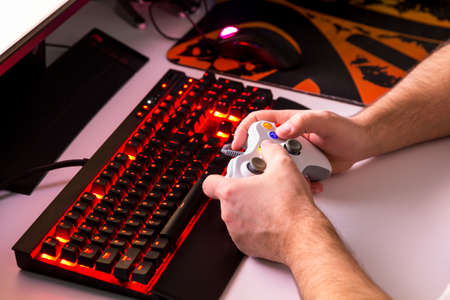 Man playing computer game on custom made desktop with joypad, keyboard, mouse. Stock Photo