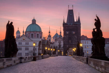 Prague, Czech Republic. Charles Bridge with its statuette and sunrise over the bridge, Old Town Bridge Tower in the background.