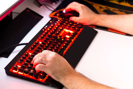 backlit keyboard: Playing computer game with gaming gear. Stock Photo