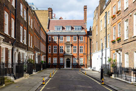 Typical street scene in the central London district with familiar architecture facades to urban housing.