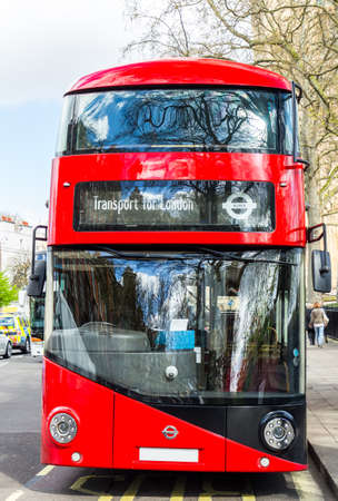 Panning shot of red double decker bus in London.