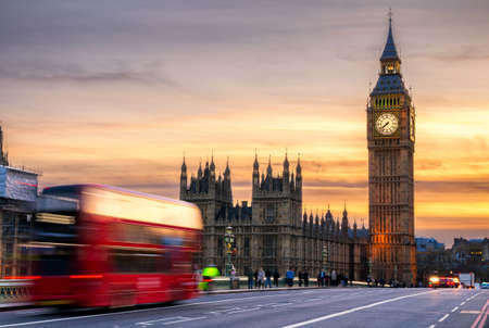 spire: London, the UK. Red bus in motion and Big Ben, the Palace of Westminster. The icons of England
