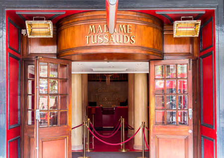 London, England - April 3, 2017: Entrance of Madame Tussauds museum with brass ensign and wooden door. Editorial