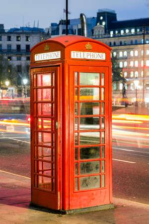 Rode telefooncel in straat met historische architectuur in Londen.