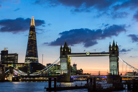tallest bridge: Tower Bridge, the Shard, city hall and business district in the background at night, London, Uk. Stock Photo
