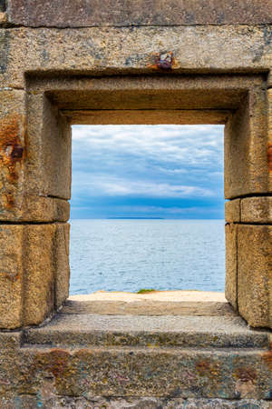 Ocean viewed through window of stone wall
