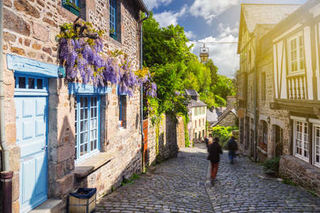 Beautiful view of scenic narrow alley with historic traditional houses and cobbled street in an old town of Dinan with blue sky and clouds. Brittany (Bretagne), France