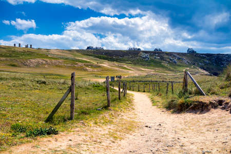 Sandy trail leading to a sunny beach in France, overseeing the ocean and blue sky. Brittany (Bretagne), France. Stock Photo
