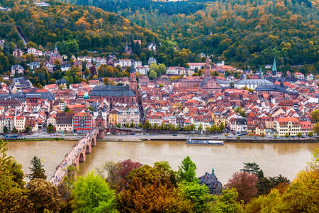 View on Heidelberg in autumn with red foliage including Carl Theodor Old Bridge, Neckar river, Church of the Holy Spirit, Germany