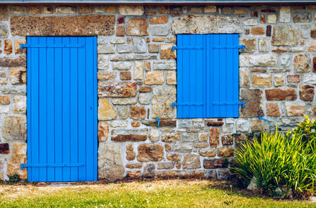Vintage blue door and window on the facade of an old cottage stone wall. Stock Photo