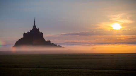 Panoramic view of famous Le Mont Saint-Michel tidal island in beautiful sunrise foggy light, Normandy, northern France Stock Photo